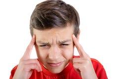 Den unga caucasian tonårs- pojken med smärtar i hans huvud arkivbild