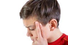 Den unga caucasian tonårs- pojken med smärtar i hans huvud royaltyfri foto