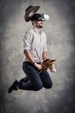 Den unga caucasian vuxna mannen tycker om att erfara immersive simulering för virtuell verklighetcowboylek VR-ståendebegrepp med royaltyfri bild