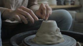 Den unga ceramisten polerar leravasen, medan sitta i modernt seminarium arkivfilmer
