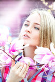Den unga charmiga damen som drömmer i vårtid med rosa färger, blommar på Arkivfoton