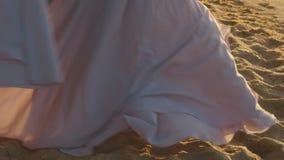 Den unga charmiga flickan i lång ljus klänning kör playfully längs coastine på den sandiga stranden på den guld- timmen lager videofilmer