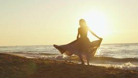 Den unga charmiga flickan i lång ljus klänning virvlar runt omkring på den sandiga stranden enlighted av guld- solnedgångstrålar arkivfilmer