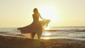 Den unga charmiga flickan i lång ljus klänning virvlar runt omkring på den sandiga stranden på den guld- timmen för solnedgången arkivfilmer