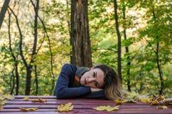 Den unga charmiga flickan med långt hår ligger på tabellen bland de stupade gula sidorna i hösten parkerar arkivfoto
