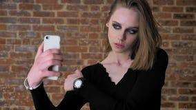 Den unga charmiga flickan med rökiga ögon gör seifie på hennes smartphone som blinkar, kommunikationsbegreppet, tegelstenbakgrund stock video