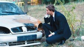 Den unga chauffören från den brända bilen Kallar försäkringmedlet Begrepp: olycka brand som är auto arkivfilmer