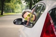 Den unga chauffören kikar från bilfönster royaltyfri foto