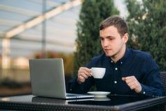 Den unga chefen som arbetar på en bärbar dator på coffeavbrott Äta lunch avbrottet Royaltyfria Bilder