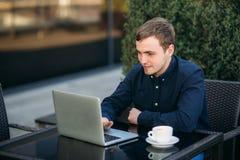 Den unga chefen som arbetar på en bärbar dator i parkera Äta lunch avbrottet Arkivbild
