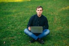 Den unga chefen som arbetar på en bärbar dator i parkera Äta lunch avbrottet Royaltyfri Fotografi
