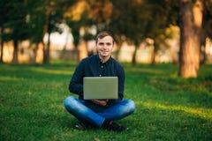 Den unga chefen som arbetar på en bärbar dator i parkera Äta lunch avbrottet Arkivfoto