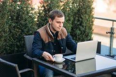 Den unga chefen som arbetar på en bärbar dator i parkera Äta lunch avbrottet Royaltyfri Foto