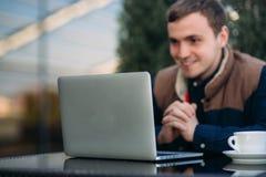 Den unga chefen som arbetar på en bärbar dator i parkera Äta lunch avbrottet Arkivfoton