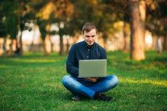 Den unga chefen som arbetar på en bärbar dator i parkera Äta lunch avbrottet Royaltyfria Foton