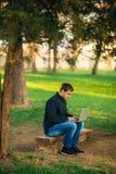 Den unga chefen som arbetar på en bärbar dator i parkera Äta lunch avbrottet Arkivbilder