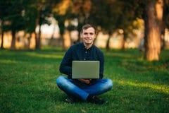 Den unga chefen som arbetar på en bärbar dator i parkera Äta lunch avbrottet Royaltyfri Bild