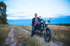 Den unga cyklisten bär det svarta läderomslaget och jeans, sitter på hans svarta gamla moped, rymmer den vita hjälmen och ser på Royaltyfria Bilder