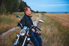 Den unga cyklisten bär det svarta läderomslaget och jeans, sitter på hans svarta gamla moped, rymmer den vita hjälmen och ser på Fotografering för Bildbyråer