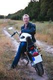 Den unga cyklisten bär det svarta läderomslaget och jeans, sitter på hans svarta gamla moped, rymmer den vita hjälmen och ser på Arkivfoto