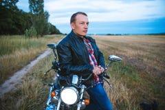 Den unga cyklisten bär det svarta läderomslaget och jeans, sitter på hans svarta gamla moped, rymmer den vita hjälmen och ser på Arkivbild