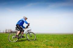 Den unga cyklisten som på våren cyklar, parkerar Arkivbilder