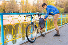Den unga cyklisten som stoppar för att binda hans sko, snör åt arkivfoton