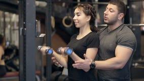 Den unga damen gör främre hantelkrullning, och den manliga instruktören rymmer hennes händer i modern idrottshall stock video