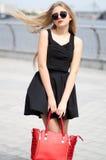Den unga damen i bkackkjol, den sleeveless skjortan och mode hänger löst posi fotografering för bildbyråer