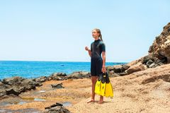 Den unga damen i dykningdräkt med skovlar som står på, vaggar kusten arkivbilder