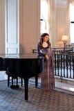 Den unga damen i en violett gammalmodig klänning med ett krås står nära pianot i den gamla inre av herrgården royaltyfri foto
