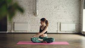 Den unga damen i moderiktigt bekläda för sportar gör kroppvridningar som sitter i lotusblommaposition på matt inre yogastudio kop lager videofilmer