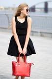 Den unga damen i svart kjol, den sleeveless skjortan och mode hänger löst posi fotografering för bildbyråer