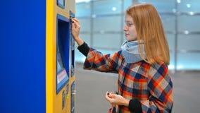 Den unga damen köper en biljett i den automatiska varuautomaten som betalar vid mynt lager videofilmer