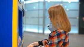 Den unga damen köper en biljett i varuautomaten som betalar vid den kontanta pengarräkningen stock video