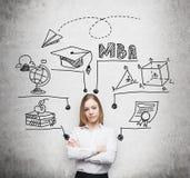 Den unga damen med korsade händer ska få filosofie magisterexamen i affärsadministration Ett begrepp av MBA degren Arkivbild