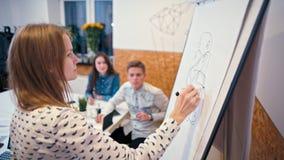Den unga damen skriver på Flipchart på mötet av affärslaget i kontoret arkivfilmer