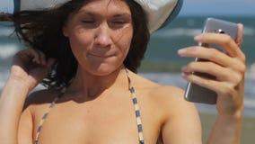 Den unga damen som delar selfie i samkväm, knyter kontakt och att tycka om hennes stag på sommarstranden lager videofilmer