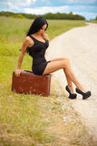 Den unga damen väntar någon bil på vägen Arkivbild