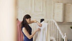 Den unga den klädformgivaren och sömmerskan syr skjortan med tråden och visaren i skräddarestudio stock video