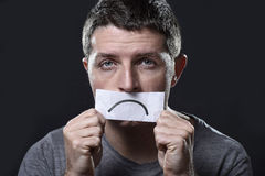 Den unga deprimerade mannen som är borttappad i sorgsenhet- och sorginnehav, skyler över brister med den ledsna munnen i fördjupn Arkivbild