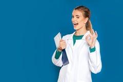 Den unga doktorn för den kvinnliga studenten med en minnestavla på en blåttbakgrundsvisning undertecknar royaltyfri foto