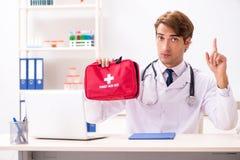 Den unga doktorn med första hjälpensatsen i sjukhus royaltyfri foto