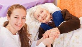 Den unga doktorn rymmer de gammalare kvinnahänderna royaltyfria bilder