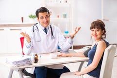 Den unga doktorn som kontrollerar kvinnas blodtryck royaltyfri foto