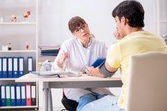 Den unga doktorn som kontrollerar patientblodtryck arkivbilder