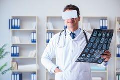 Den unga doktorn som ser mribildläsning till och med vrexponeringsglas Fotografering för Bildbyråer
