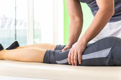 Den unga doktorskiropraktorn som masserar patienten royaltyfria foton