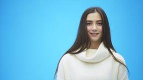 Den unga driftiga flickan står på en blå bakgrund Under detta ler, efter att ha justerat hår lager videofilmer
