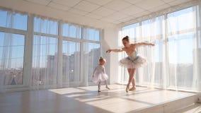 Den unga eleganta ballerina undervisar hennes lilla dotterdans i studio lager videofilmer